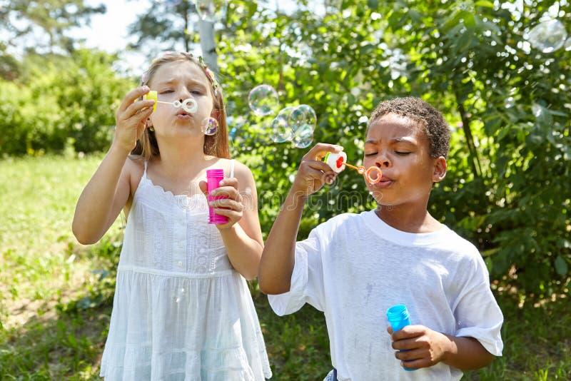 La muchacha y el muchacho están soplando burbujas juntas fotografía de archivo
