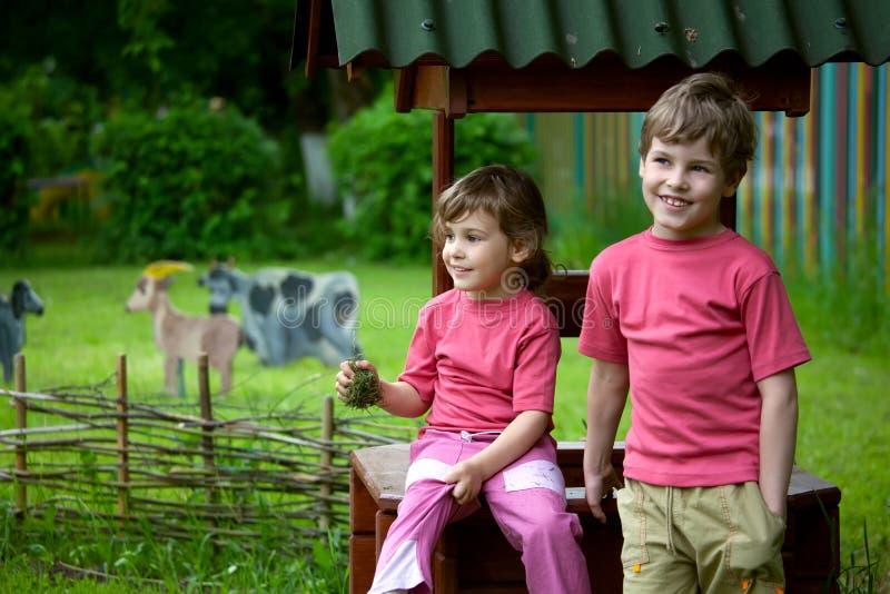 La muchacha y el muchacho se sientan en un receptor de papel imagen de archivo libre de regalías