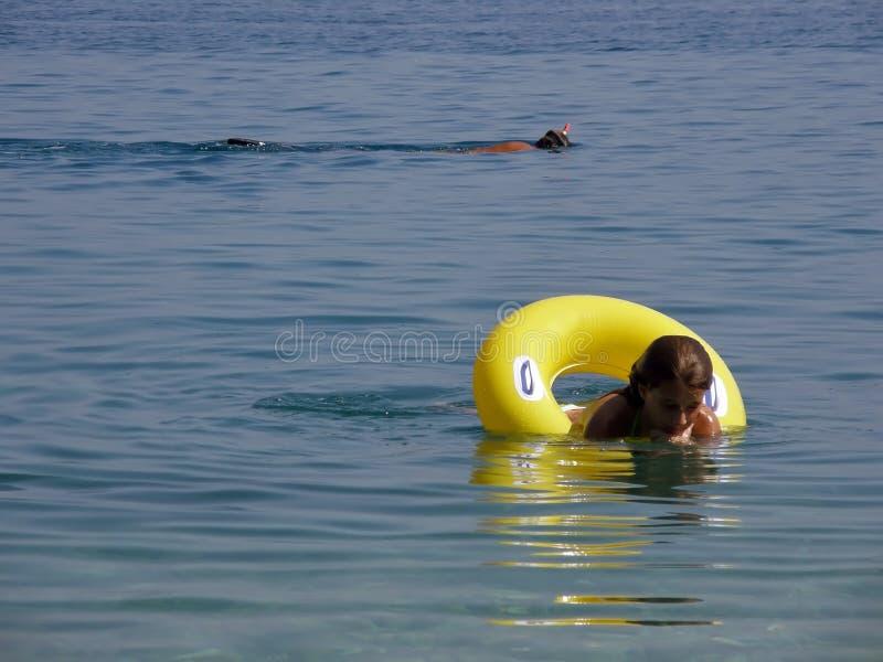 La muchacha y el zambullidor gozan en el mar foto de archivo