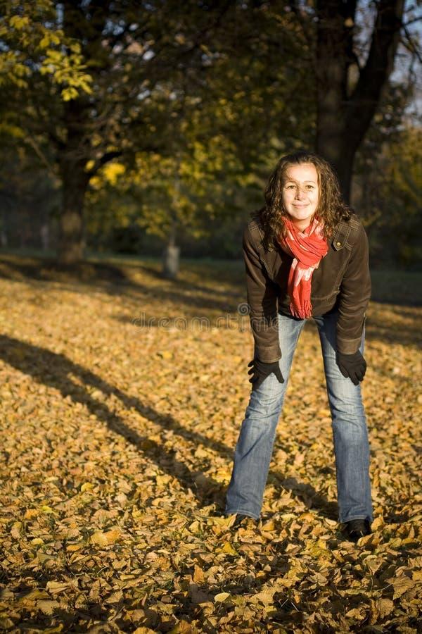 La muchacha y las hojas imagen de archivo