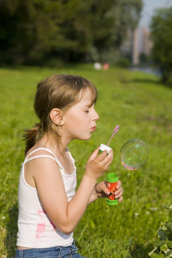 La muchacha y una burbuja de jabón imagen de archivo