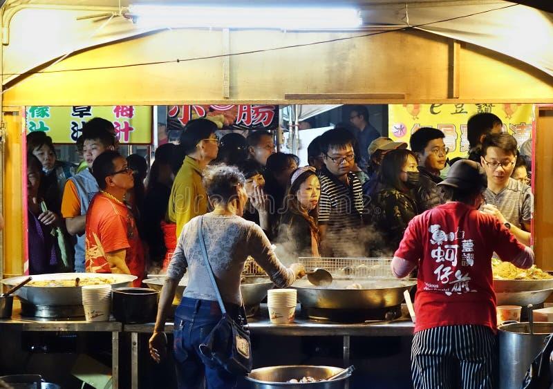 La muchedumbre de gente visita las paradas de la comida fotografía de archivo