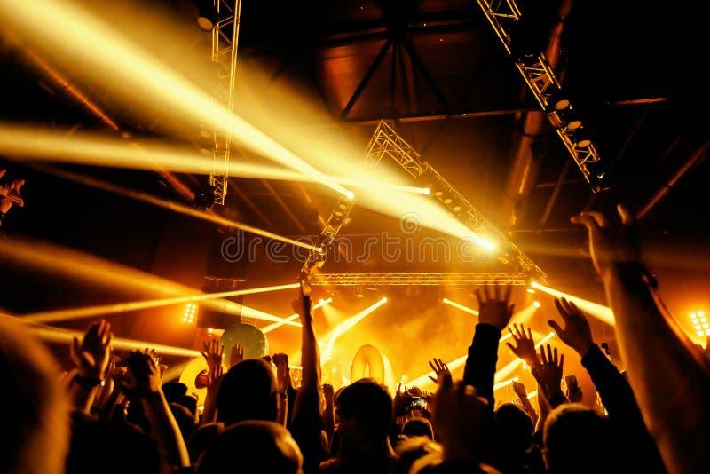 La muchedumbre de la silueta del club de noche da para arriba con el entertanment de la mosca imágenes de archivo libres de regalías