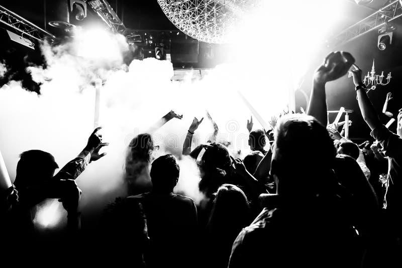 La muchedumbre de la silueta del club de noche da para arriba en la etapa del vapor del confeti fotos de archivo