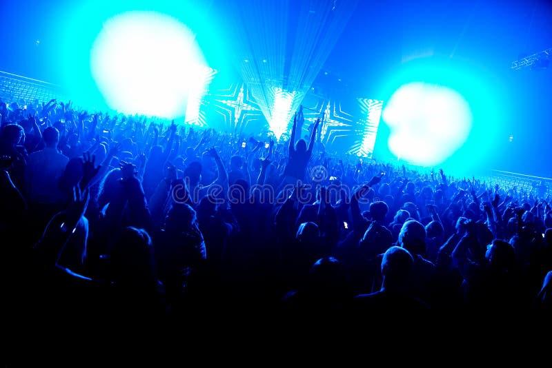 La muchedumbre de la silueta del club de noche da para arriba en la etapa del vapor del confeti foto de archivo libre de regalías