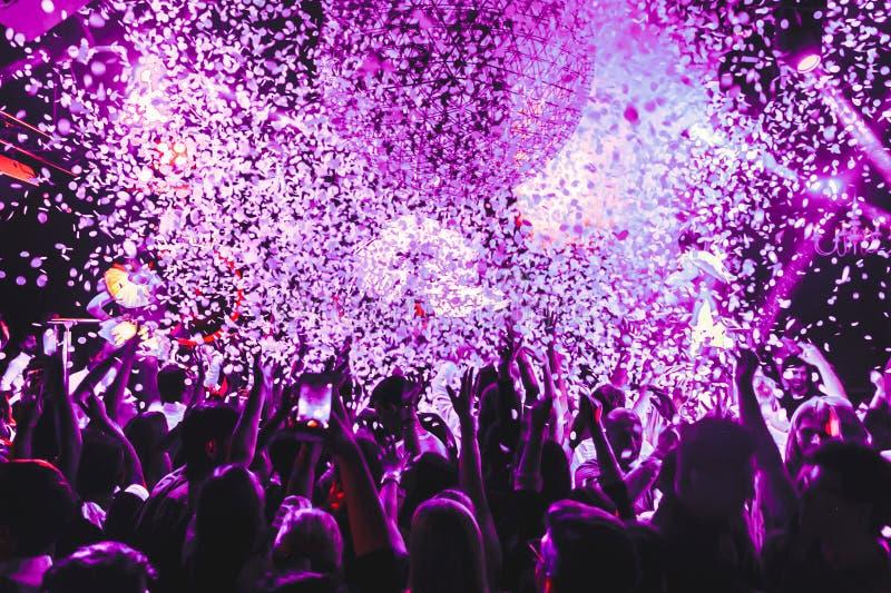 La muchedumbre de la silueta del club de noche da para arriba en la etapa del vapor del confeti imagenes de archivo