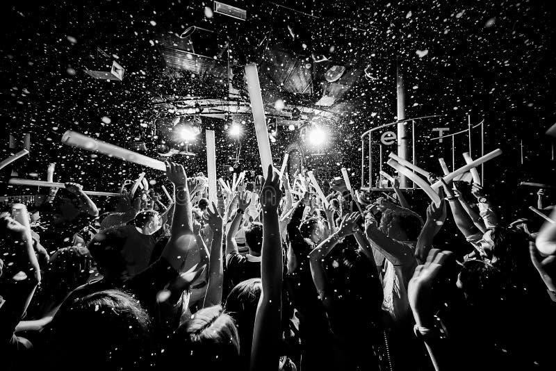La muchedumbre de la silueta del club de noche da para arriba en la etapa del vapor del confeti imágenes de archivo libres de regalías