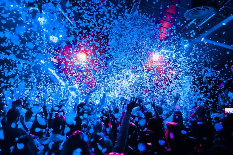 La muchedumbre de la silueta del club de noche da para arriba en la etapa del vapor del confeti fotografía de archivo libre de regalías