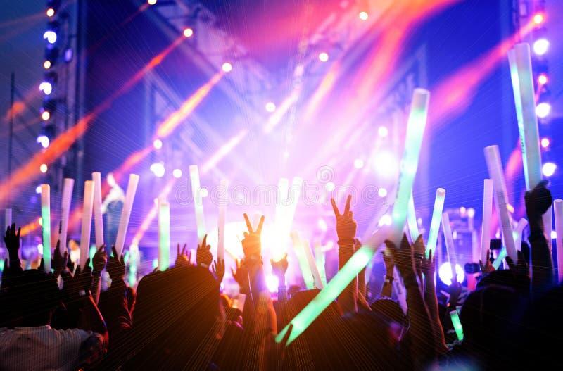 La muchedumbre de manos sube luces de la etapa del concierto foto de archivo libre de regalías