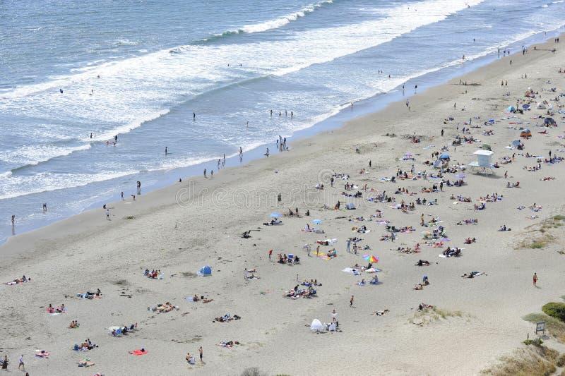 La muchedumbre disfruta de una playa y de una resaca imágenes de archivo libres de regalías