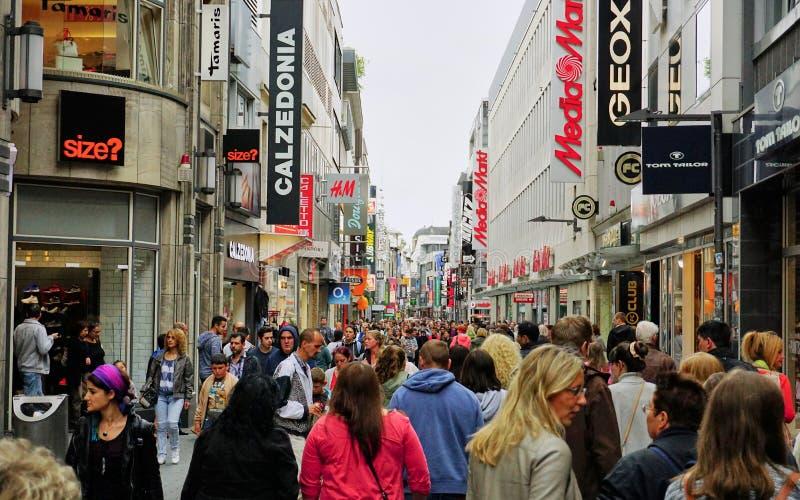 La muchedumbre diversa llena la calle principal del distrito que hace compras en Colonia, Alemania foto de archivo