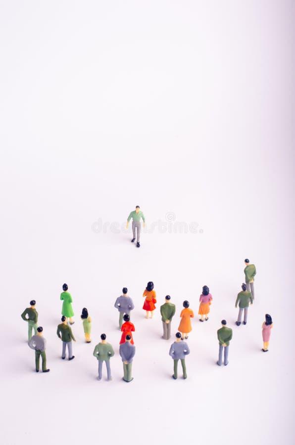 La muchedumbre está mirando al hombre que viene hacia ella en un fondo blanco El hombre se está acercando a un grupo de personas  fotos de archivo libres de regalías