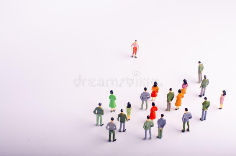 La muchedumbre mira a la mujer que está caminando hacia ella en un fondo blanco Una mujer se está acercando a un grupo de persona fotos de archivo