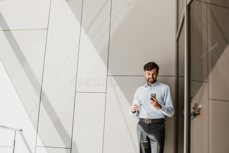 La mueca del hombre de negocios está utilizando el teléfono durante tiempo libre imagenes de archivo