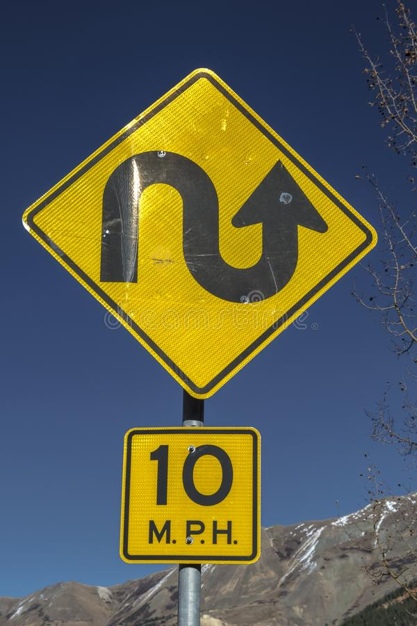 La muestra amarilla advierte a conductores retrasar en el camino escarpado de la montaña imagen de archivo