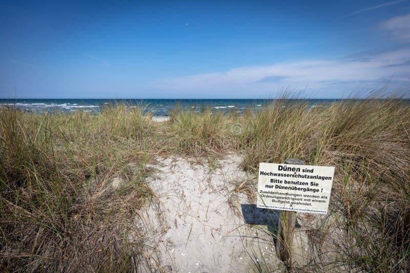 La muestra con una señal de peligro se coloca en la duna del SE báltico foto de archivo
