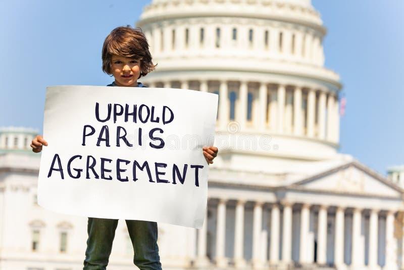 La muestra de la tenencia del manifestante mantiene el acuerdo de París en manos imagen de archivo libre de regalías