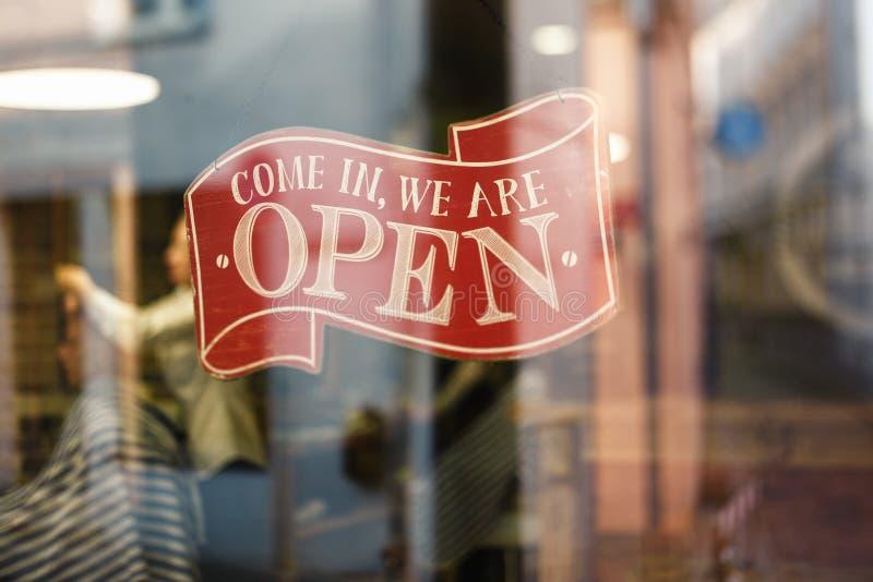La muestra del vintage del negocio que dice venido en nosotros está abierta en el peluquero y la ventana de la tienda de la peluq foto de archivo