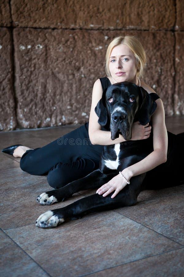 La mujer abraza un perro imagenes de archivo