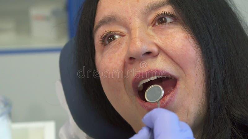La mujer abre su boca para el control dental imagenes de archivo