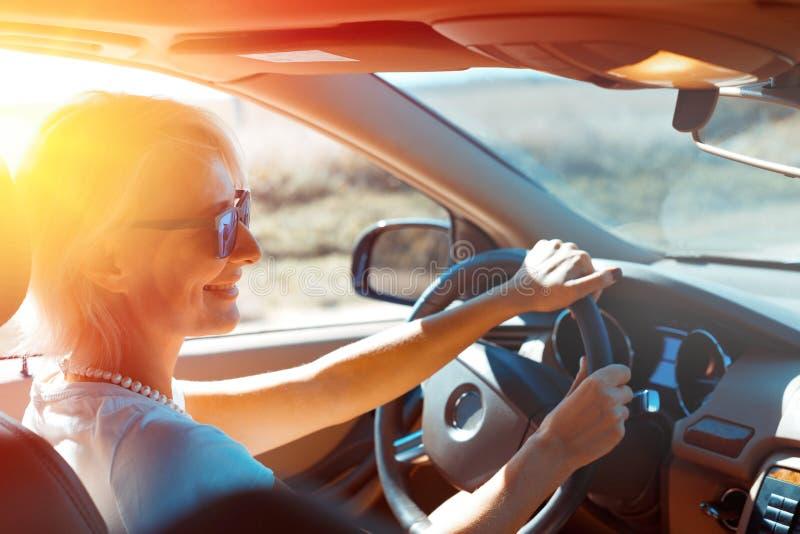 La mujer acertada feliz goza el conducir en una aventura del camino Holid foto de archivo