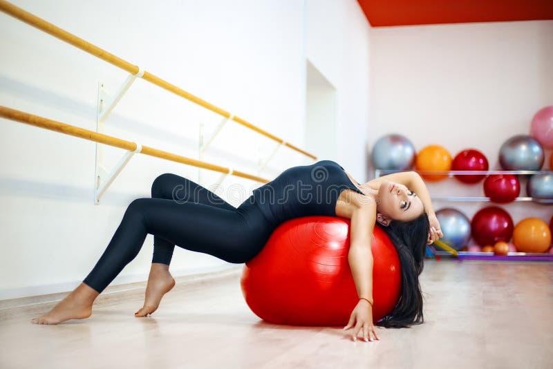 La mujer activa joven en una camiseta y polainas, realiza ejercicios el estirar y de la yoga en un estudio moderno foto de archivo