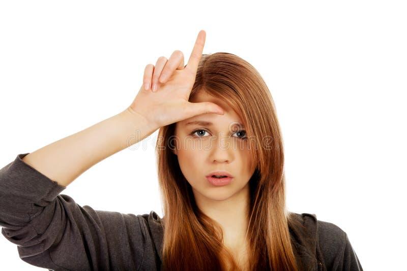 La mujer adolescente hace la muestra del perdedor en su frente imágenes de archivo libres de regalías