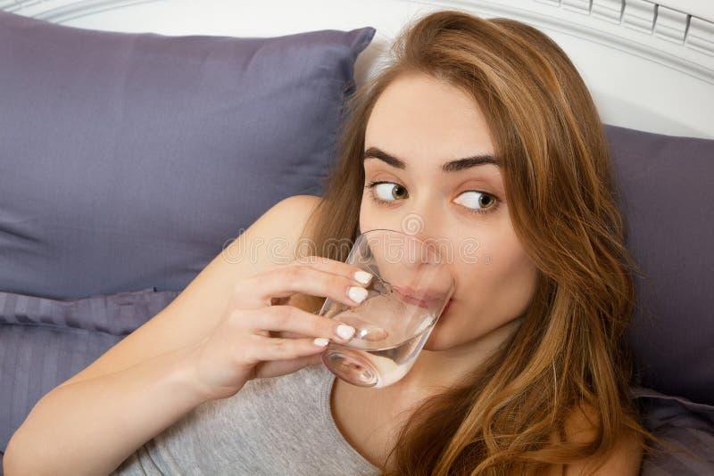 La mujer adolescente hermosa bebe el agua por la mañana en cierre de la cama para arriba fotos de archivo