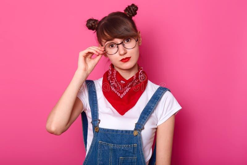 La mujer adorable joven lleva los guardapolvos del dril de algodón, camiseta blanca casual, pañuelo rojo en cuello y redondeó las imágenes de archivo libres de regalías