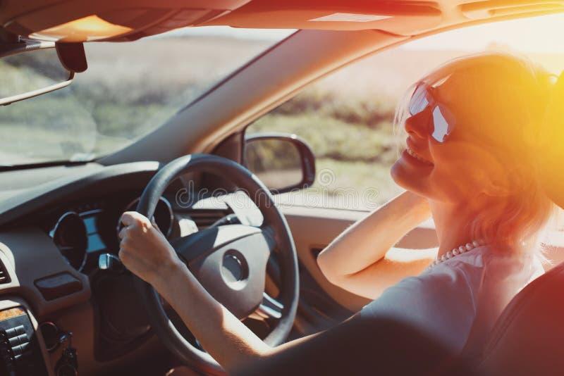 La mujer adulta acertada feliz goza el conducir en una aventura del camino Concepto del viaje de las vacaciones del día de fiesta foto de archivo libre de regalías