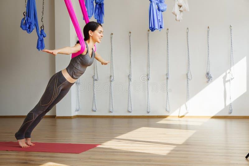 La mujer adulta practica la aero- posición antigravedad de la yoga en estudio foto de archivo libre de regalías