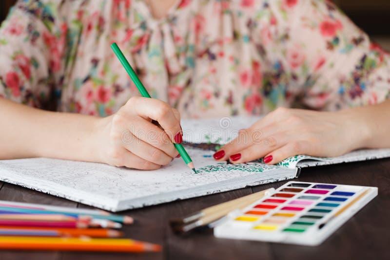 La mujer adulta se relaja por el libro de colorear que duele foto de archivo
