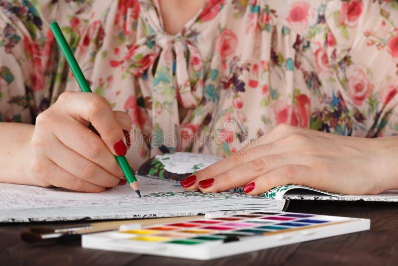 La mujer adulta se relaja por el libro de colorear que duele imagen de archivo libre de regalías