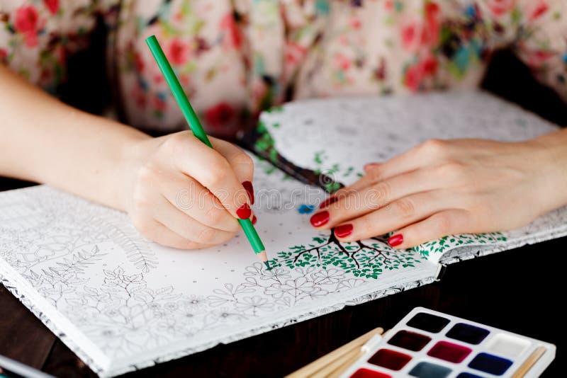 La mujer adulta se relaja por el libro de colorear que duele imagen de archivo