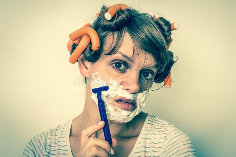 La mujer afeita su cara con la espuma y la maquinilla de afeitar - estilo retro fotos de archivo libres de regalías