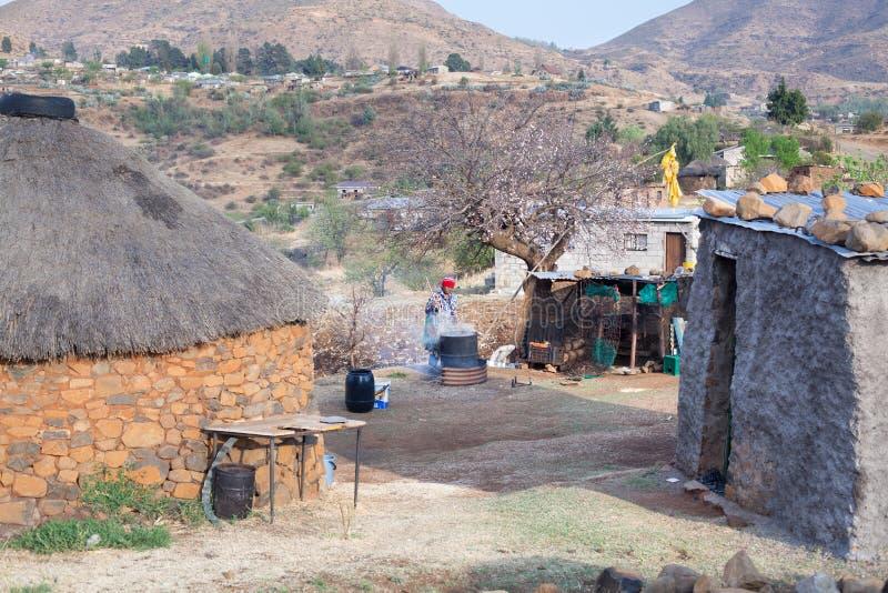 La mujer africana adulta en vestido combinado tradicional elabora cerveza la bebida nacional en barril del metal en el patio del  fotos de archivo libres de regalías
