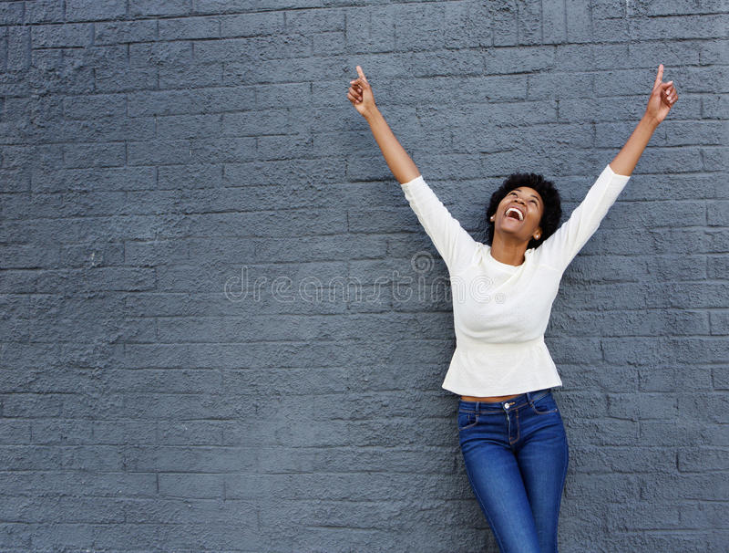 La mujer africana alegre con las manos planteó el tema para arriba fotos de archivo