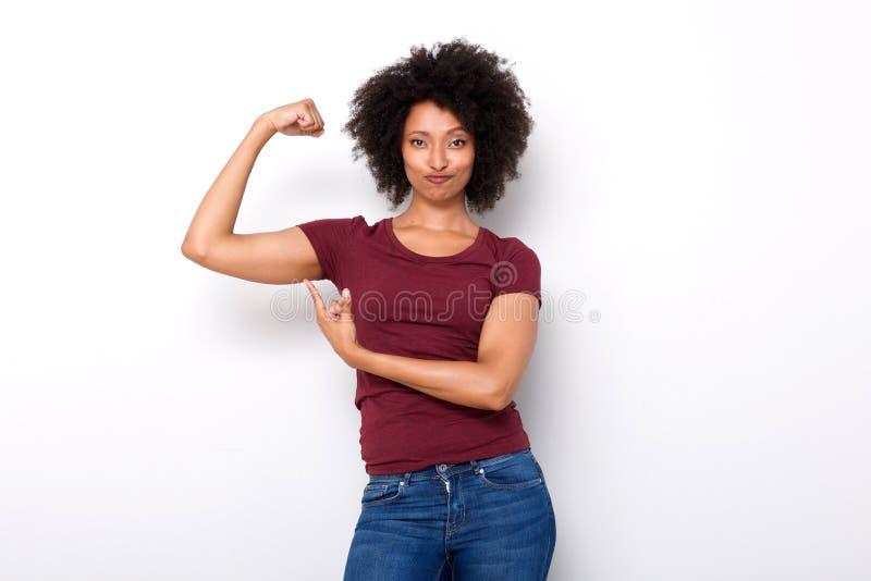 La mujer africana joven apta que señala en el brazo muscles en el fondo blanco foto de archivo