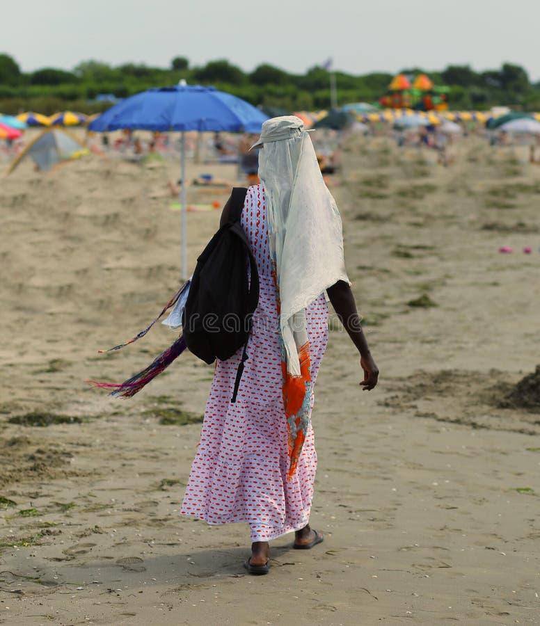 La mujer africana peina el pelo con las trenzas coloridas en la playa en su imagen de archivo libre de regalías