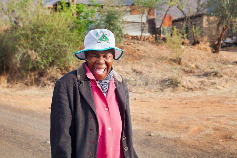 La mujer africana sonriente divertida adulta en vestido brillante en la calle auténtica del pueblo, vieja mujer de risa feliz del foto de archivo libre de regalías