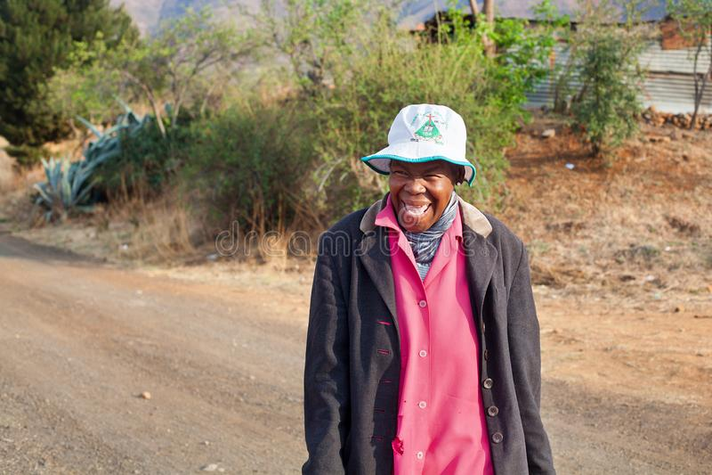 La mujer africana sonriente divertida adulta en vestido brillante en la calle auténtica del pueblo, vieja mujer de risa feliz del foto de archivo