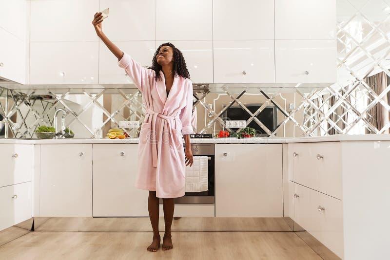 La mujer africana sonriente hermosa con el pelo rizado en albornoz rosada está tomando el selfie en el teléfono móvil Cocina mode imagen de archivo