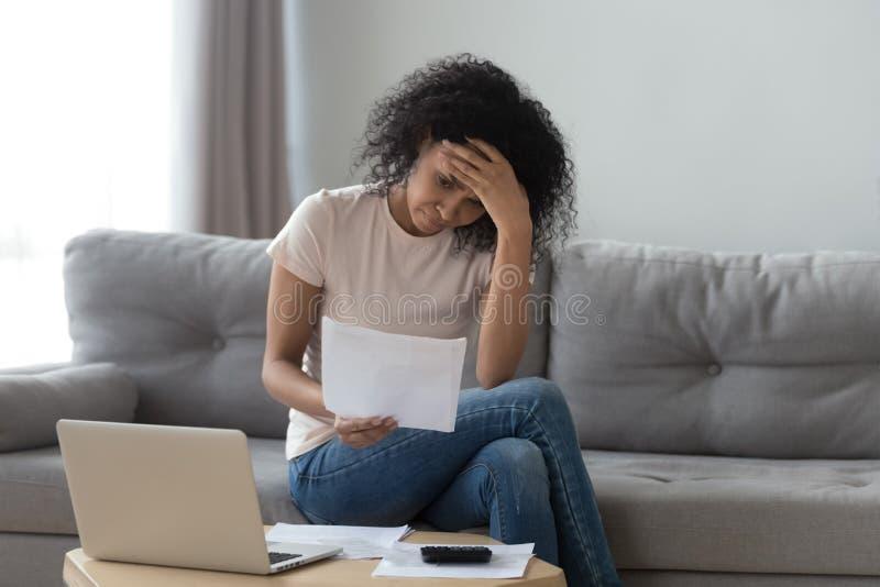 La mujer africana subrayada que llevaba a cabo cuentas se preocupó de deuda de banco de la quiebra imagenes de archivo
