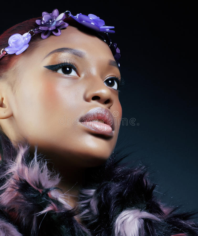 La mujer afroamericana bonita joven en abrigo de pieles manchado y la joyería de las flores en etnic dulce sonriente de la cabeza imagen de archivo