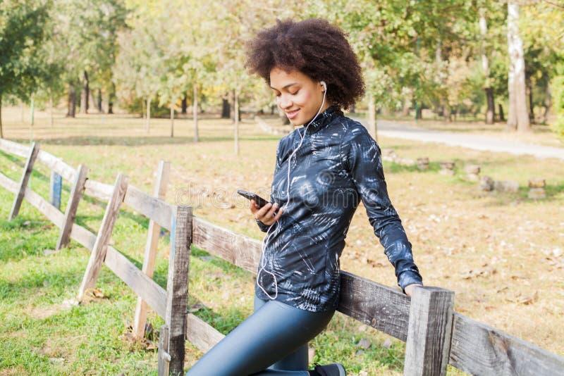 La mujer afroamericana deportiva relaja música que escucha después del entrenamiento en el parque foto de archivo