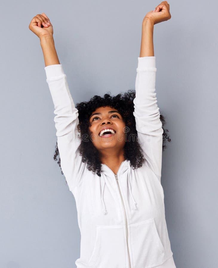 La mujer afroamericana joven alegre que reía con los brazos aumentó contra fondo gris imagenes de archivo