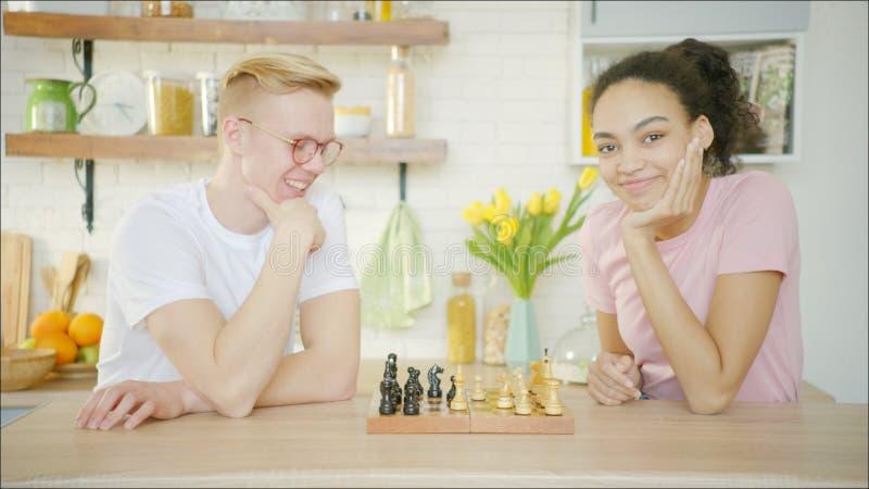 La mujer afroamericana joven de dos amigos y el hombre rubio están jugando a ajedrez imagen de archivo libre de regalías