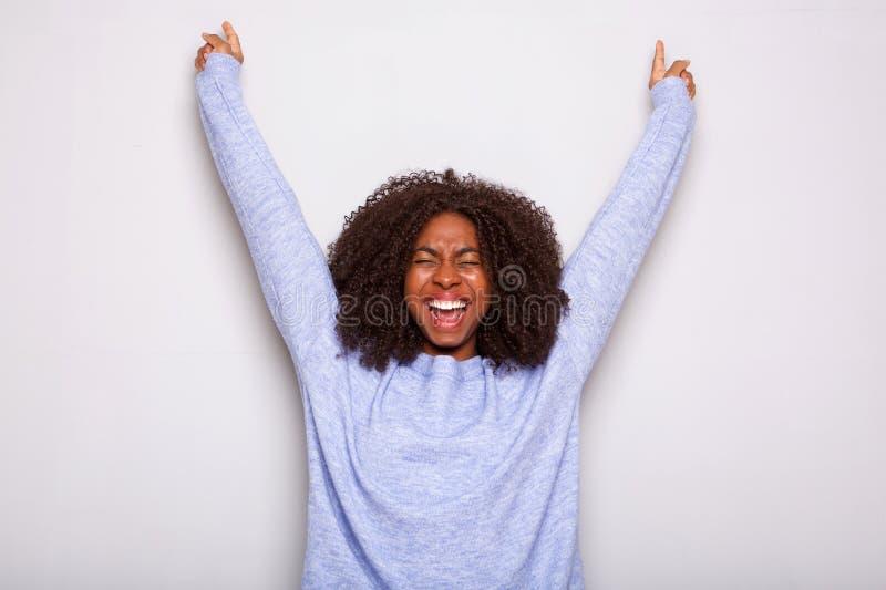 La mujer afroamericana joven emocionada que animaba con las manos aumentó contra el fondo blanco fotos de archivo libres de regalías