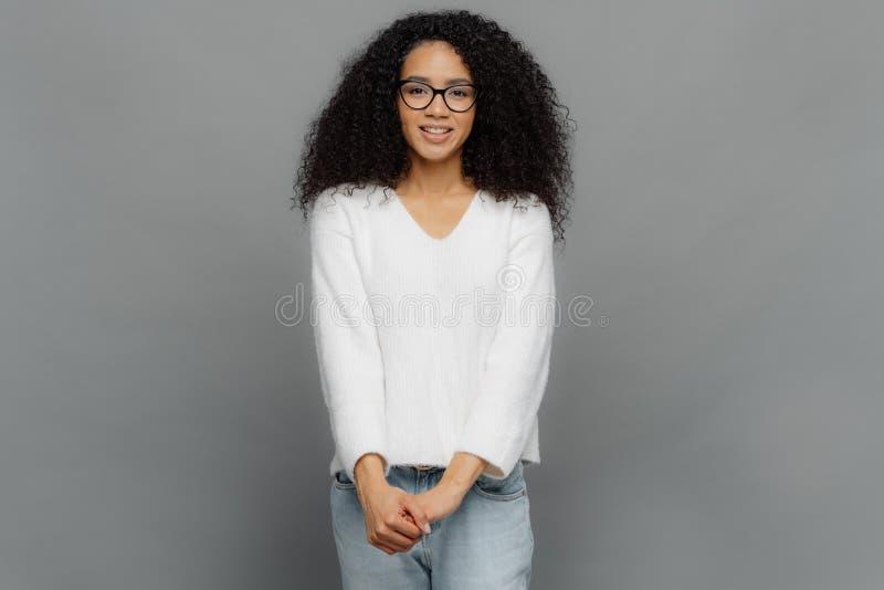 La mujer afroamericana joven satisfecha mantiene las manos juntas, las sonrisas suavemente, vestido suéter blanco casual y vaquer fotos de archivo libres de regalías