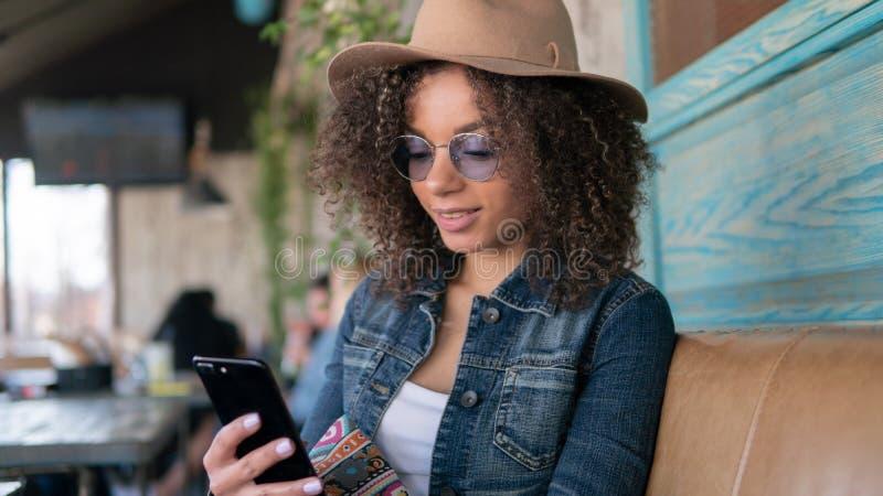 La mujer afroamericana linda charla en los vidrios y el sombrero, café interior de Internet, el llevar fotografía de archivo libre de regalías